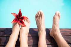 Couple bare feet against swimming pool Royalty Free Stock Photography