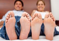 Couple barefoot on the bed Stock Photos