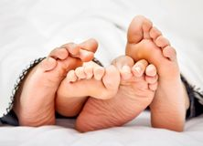 Couple barefoot in bed Royalty Free Stock Photos