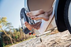 Couple of barefooted travelers lying in their compact trailer standing near beach. Barefooted travelers. Cute loving couple of barefooted travelers lying in stock photography