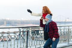 Couple at barrier looking in far. Woman shows to man. Lady pointing by hands and man looking after. City tourists find interesting Royalty Free Stock Images