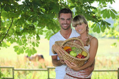 Couple with a basket of fruits Stock Image