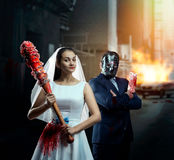 Couple with bat and meat cleaver in night city. Maniac couple with bloody bat and meat cleaver in night city. Groom in hockey mask stock images