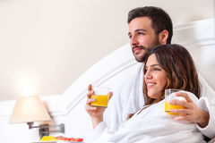 Couple in bathrobe drinking orange juice. Stock Image