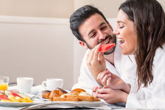 Couple in bathrobe having fun eating fruit. Royalty Free Stock Images