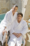 Couple In Bathrobe Sitting On Chair By Pool Royalty Free Stock Photos