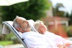 Couple in bathrobe sleeping in long chairs Stock Image