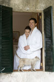 Couple in bathrobes and cat on windowsill Royalty Free Stock Photography