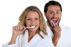 Couple in bathrobes cleaning teeth Stock Photos