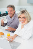 Couple in bathrobes with coffee and juice using laptop in kitchen. Couple in bathrobes with coffee and juice using laptop in the kitchen at home royalty free stock photo