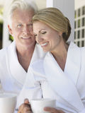 Couple In Bathrobes With Cups On Verandah Royalty Free Stock Photography