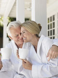 Couple In Bathrobes With Cups On Verandah Stock Images
