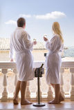 Couple in bathrobes drinking champagne on balcony Stock Images