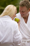 Couple in bathrobes eating apple Royalty Free Stock Images