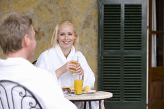 Couple in bathrobes eating breakfast on patio Stock Image