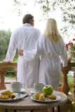 Couple in bathrobes eating breakfast on patio Stock Images