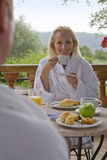 Couple in bathrobes eating breakfast on patio Royalty Free Stock Photo