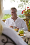 Couple in bathrobes eating breakfast on patio Royalty Free Stock Image