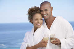 Couple In Bathrobes Holding Drinks Stock Images