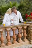 Couple in bathrobes hugging and drinking orange juice on balcony Royalty Free Stock Images