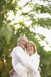 Couple In Bathrobes Hugging By Palm Trees Stock Photo