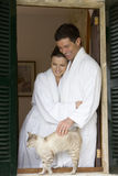 Couple in bathrobes petting cat on windowsill Royalty Free Stock Image