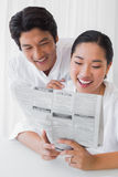 Couple in bathrobes reading newspaper together in the morning Stock Image