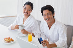 Couple in bathrobes shopping online in the morning Stock Photography