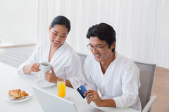 Couple in bathrobes shopping online in the morning Royalty Free Stock Images