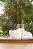 Couple In Bathrobes Sitting Back To Back By Pool Royalty Free Stock Images