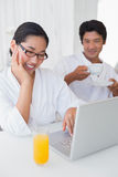 Couple in bathrobes spending the morning together using laptop Royalty Free Stock Images