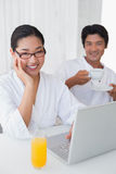 Couple in bathrobes spending the morning together using laptop Royalty Free Stock Photos