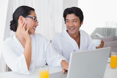 Couple in bathrobes spending the morning together using laptop Stock Images