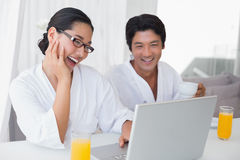 Couple in bathrobes spending the morning together using laptop Royalty Free Stock Photography