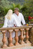 Couple in bathrobes standing at balcony railing Royalty Free Stock Images