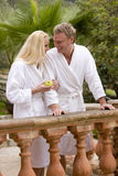 Couple in bathrobes standing at railing and holding apple Stock Photos