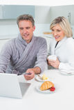 Couple in bathrobes using laptop in kitchen Royalty Free Stock Photo