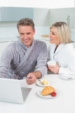 Couple in bathrobes using laptop in kitchen Stock Photos