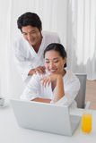 Couple in bathrobes using laptop together in the morning Royalty Free Stock Images