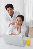 Couple in bathrobes using laptop together in the morning Royalty Free Stock Photo