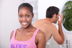 Couple in the bathroom. Black women and his boyfriend in the bathroom, the men has a wash Stock Photos