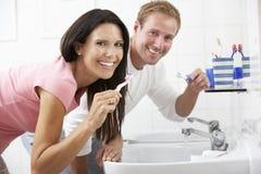 Couple In Bathroom Brushing Teeth Royalty Free Stock Photography