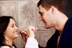 Couple in the bathroom brushing teeth. Royalty Free Stock Photo