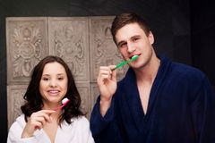 Couple in the bathroom brushing teeth. Royalty Free Stock Images