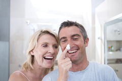 Couple in bathroom, woman putting shaving foam on man's nose, smiling Stock Photos
