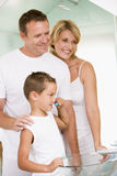 Couple in bathroom with young boy brushing teeth stock photo