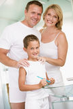 Couple in bathroom with young boy brushing teeth Royalty Free Stock Images