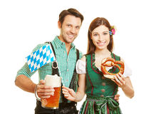 Couple in bavaria to Oktoberfest. Smiling couple in bavaria to Oktoberfest with beer and pretzel Royalty Free Stock Image