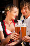 Couple in Bavarian Tracht clinking glasses. Couple in traditional Bavarian Tracht - Dirndl and Lederhosen - in front of a beer tent at the Oktoberfest or in a Stock Image