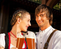 Couple in Bavarian Tracht clinking glasses. Couple in traditional Bavarian Tracht - Dirndl and Lederhosen - in front of a beer tent at the Oktoberfest or in a Stock Photography